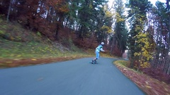 POV of young men longboard skateboarding downhill on a rural road. Stock Footage