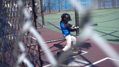 A boy practices baseball at a batting cage. Stock Footage