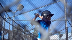 A boy practices baseball at a batting cage, super slow motion. Stock Footage
