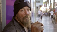 Gritty white man with beard smoking marijuana cigarette joint in street LA Stock Footage