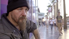 Close-up of homeless man with beard staring in street sitting on sidewalk LA Stock Footage