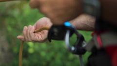 A man belays a rock climber up a mountain, detail of belay device. Stock Footage