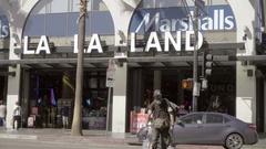 Strange man crossing street, La La Land and Marshall's store on Hollywood LA Stock Footage