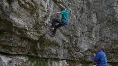 A man belays a rock climber up a mountain. Stock Footage