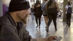 Homeless man sitting on sidewalk holding 20 dollar bill staring into space LA Stock Footage