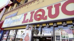 Hollywood Liquor panning across sign on boulevard in Los Angeles California Stock Footage