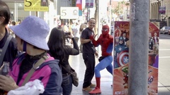Tourist taking picture with Spider-Man on Walk of Fame Hollywood Boulevard LA Stock Footage