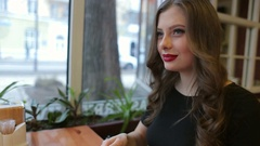 The girl drinks coffee. Beautiful girl with red lips sitting in a cafe. Stock Footage