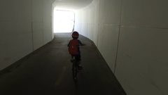 A boy rides his mountain bike through a tunnel on a paved trail in the woods. Stock Footage