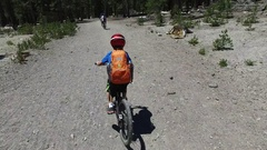 A boy rides his mountain bike on a singletrack dirt trail in the woods, time-lap Stock Footage