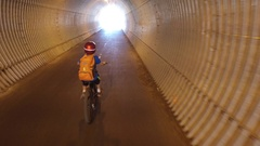 A boy rides his mountain bike through a tunnel on a paved trail in the woods, ti Stock Footage
