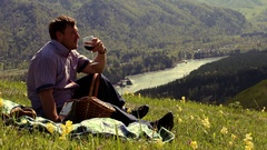 Caucasian man sitting in the mountains and enjoy the beauty of nature Stock Footage