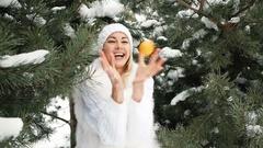 Beautiful blonde eats tangerine against background of winter landscape Stock Footage