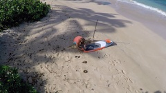 Aerial view of a man getting ready to go sup stand-up paddleboard surfing in Haw Stock Footage