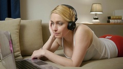 Woman with laptop and headphones lying on couch Stock Footage