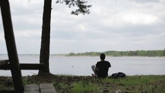 A young man relaxes on the lake shore. Man outdoors. Stock Footage