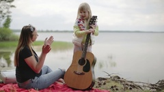 Slow motion. Blonde girls standing and playing the guitar her mother. Pregnant w Stock Footage