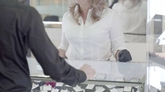 The seller in a jewelry store shows the buyer jewelery precious ring Stock Footage