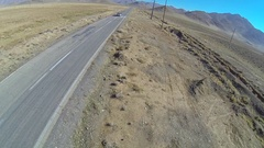 Aerial view of an empty desert road and a drone pilot, slow motion. Stock Footage