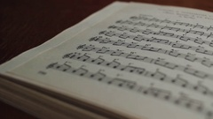Book of musical notes of classical pieces on the table in the classroom Stock Footage