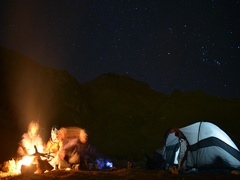 A campfire near a tent and campground at night, time-lapse. Stock Footage