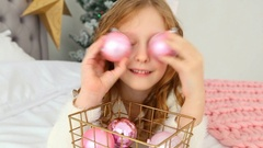 Child paying with holiday decorations, making eye with pink balls Stock Footage