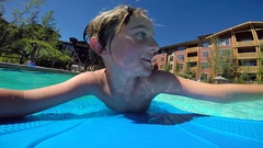 POV of a boy playing in a pool at a hotel resort. Stock Footage