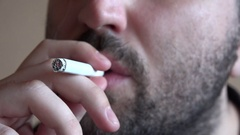 Close up 4K man smoking hard from a joint cigarette nose nostrils smoke out Stock Footage