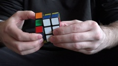 4K closeup hands playing with rubik cube thinking toy brain puzzle smart child Stock Footage