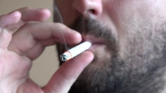 Portrait of black beard young man smoking cigarette 2 smokes inhale closeup view Stock Footage
