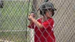 A boy practices baseball at the batting cages, super slow motion. Stock Footage