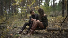 Close up of happy couple having a date in the forest. Smiling man and woman are Stock Footage