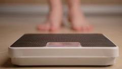 A man standing on weight scale Stock Footage