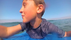 POV view of a boy and his father body boarding in the waves at the beach, super Stock Footage