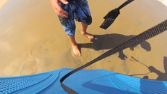 POV view of a boy putting on a leash for body boarding in the waves at the beach Stock Footage
