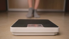 Caucasian female girl stands on the scales Stock Footage