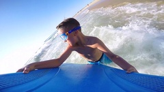 POV view of a boy wearing goggles while body boarding in the waves at the beach, Stock Footage