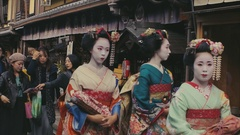 Geishas Walk Down Kyoto Street Stock Footage