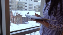 A girl stands, holding a Notepad in hand and writes Stock Footage