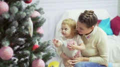 Happy young mother playing with her sweet baby in a decorated room near the Stock Footage