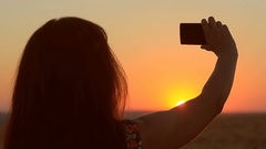 Young girl making photo on the phone at sunset, silhouette of the girl against Stock Footage