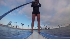 POV of a woman and dog paddling an SUP stand-up paddleboard on a lake, time-laps Stock Footage
