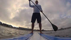 POV of a man paddling an SUP stand-up paddleboard on a lake, time-lapse. Stock Footage