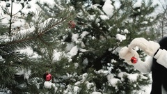 Woman decorates snowy fir-tree with red Christmas toy outdoors Stock Footage