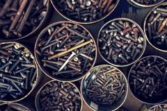 Filtered screws and bolts in tin can on wooden background Stock Photos