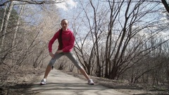 The girl athlete stretching in the Park before the run Stock Footage