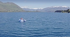 Aerial over young girls on a paddleboat in lake wanaka, New Zealand Stock Footage