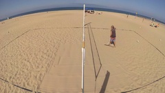 A man rakes a beach volleyball court. Stock Footage