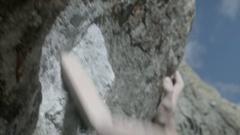 A man brushes rock befpre climbing bouldering up a mountain. Stock Footage