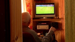 Old man watching the football championship on TV. Arkistovideo